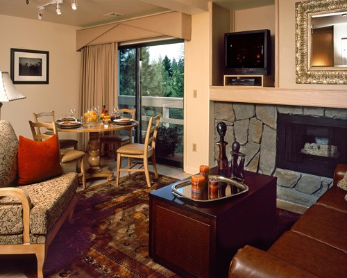 An open plan living and dining area with a television fireplace and an outside view.