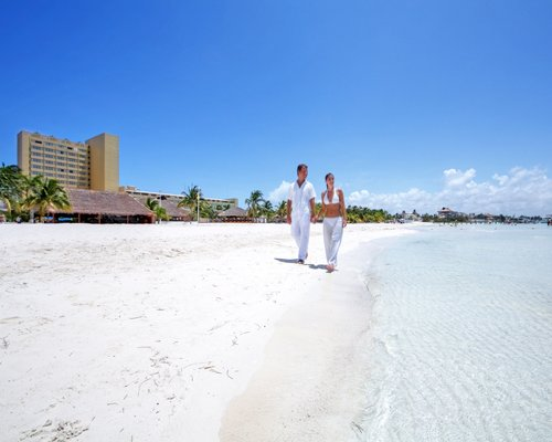 A couple walking on the beach alongside the waterfront.