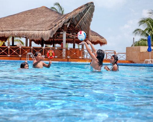 View of peoples playing volleyball on an outdoor pool.