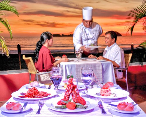 Chef serving food to a couple at the outdoor restaurant with ocean view.