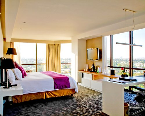 A well furnished bedroom with a double bed television and an outside view.
