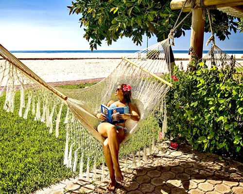 A lady in a hammock alongside the beach.