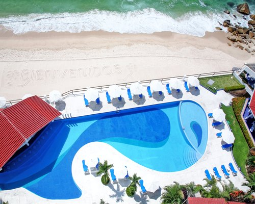 An aerial view of an outdoor swimming pool with chaise lounge chairs and sunshades alongside the waterfront.