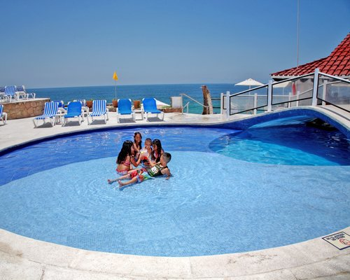 A family enjoying in an outdoor swimming pool.