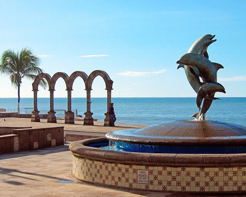 A view of dolphin statue alongside the beach.