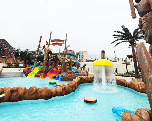 An outdoor water park with a mushroom umbrella fountain.