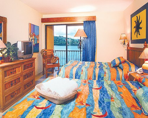 A well furnished bedroom with two twin beds television balcony and a waterfront view.