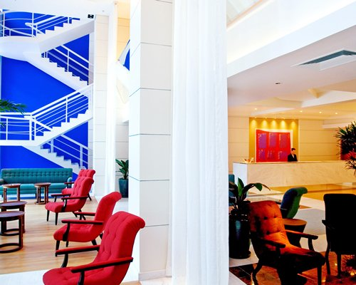 Reception and lounge area at Pestana Curitiba Hotel with a stairway.