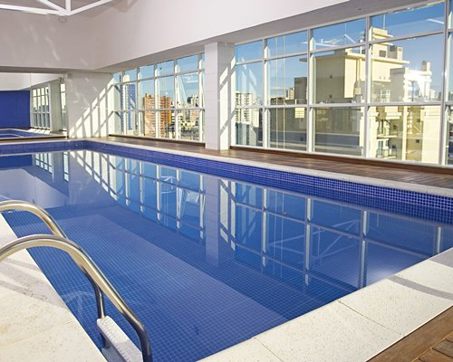 Indoor swimming pool with outside view.