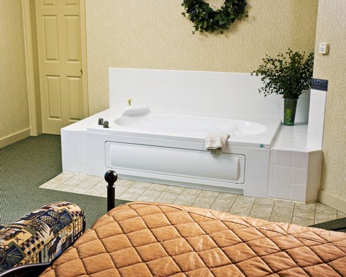 A well furnished bedroom with bathtub.