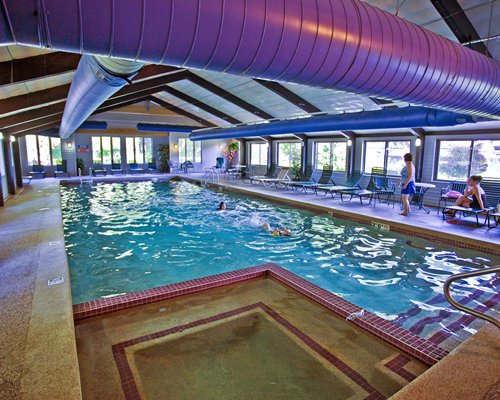 An indoor swimming pool with hot tub chaise lounge chairs and an outside view.