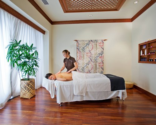A woman enjoying a massage in an indoor spa room.