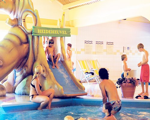 People at an indoor swimming pool with a slide.