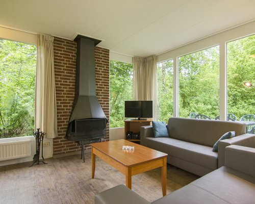A well furnished living room with a television fireplace and an outside view.