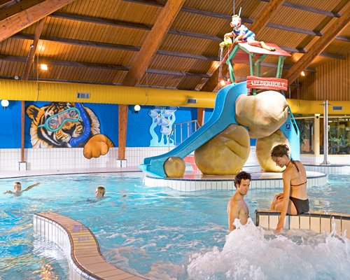 An indoor swimming pool with kids playscape.