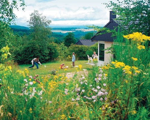 A family playing in the picnic area of the resort and flowering shrubs.