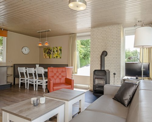 An open plan living and dining area with a television and fireplace.
