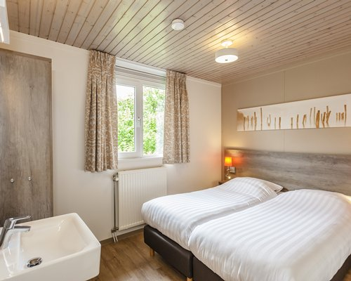 A well furnished bedroom with two twin beds sink and an outside view.