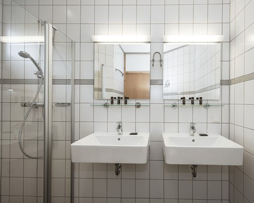 A bathroom with a double sink vanity and stand up shower.