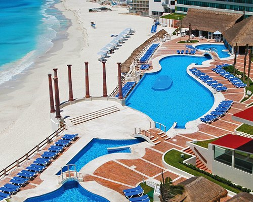 An aerial view of an outdoor swimming pool with chaise lounge chairs alongside the beach.