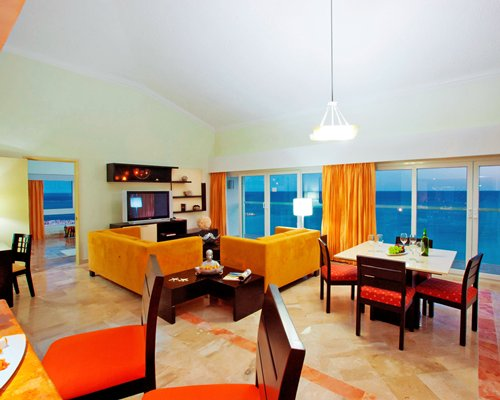An open plan living and dining area with a television and the beach view.