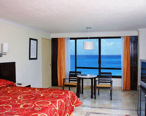 A well furnished bedroom with a television and the ocean view.