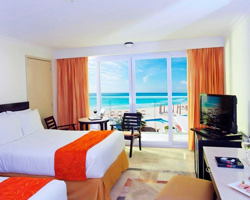 A well furnished bedroom with two beds a television and outside view.