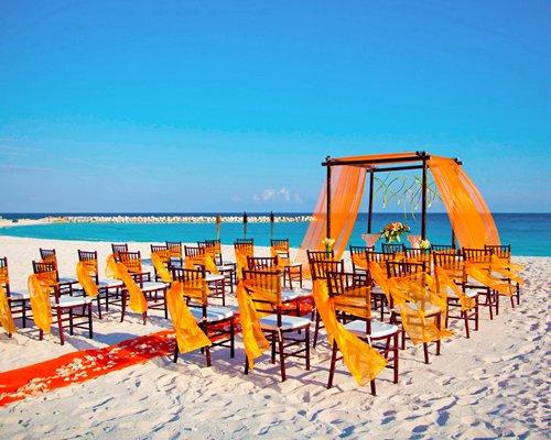 Decorated wedding venue at the beach alongside the ocean.
