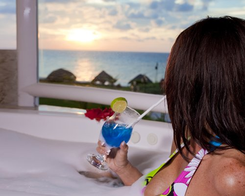 A woman drinking cocktail with an outside view.