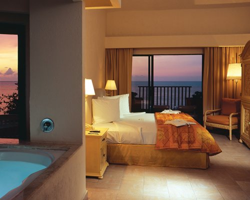 A well furnished bedroom with a king bed bathtub and ocean view.