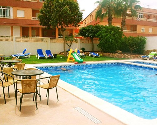 An outdoor swimming pool with patio furniture alongside multi story resort units.