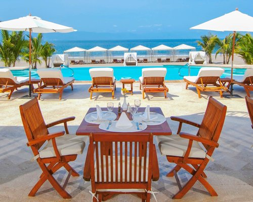 An outdoor dining area alongside the swimming pool with chaise lounge chairs and sunshades.