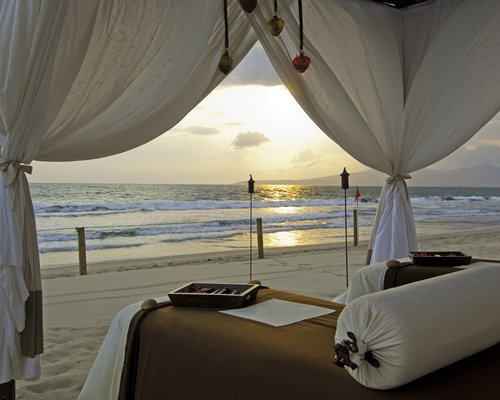 Outdoor spa with massage bed alongside the ocean.