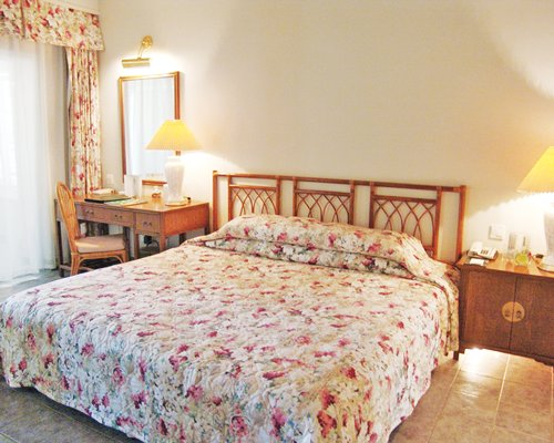 A well furnished bedroom with a double bed and a vanity.