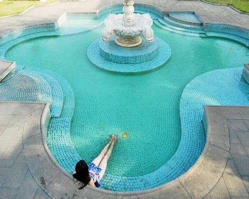 An outdoor swimming pool with a fountain.