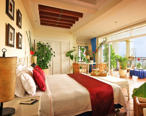 A well furnished bedroom with a balcony and potted plants.