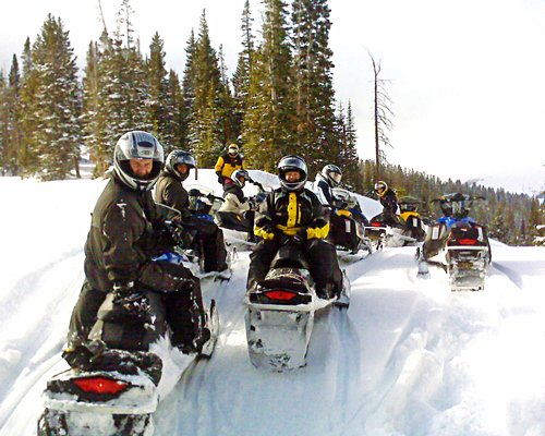 Group of people riding snowmobiles.