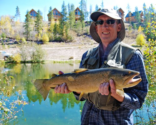 A man holding a large fish alongside the resort.