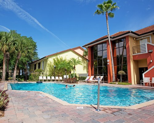 Scenic view of Legacy Vacation Club Lake Buena Vista with outdoor swimming pool and chaise lounge chairs.
