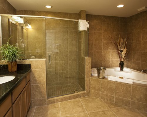 A bathroom with shower stall bathtub and closed sink vanity.