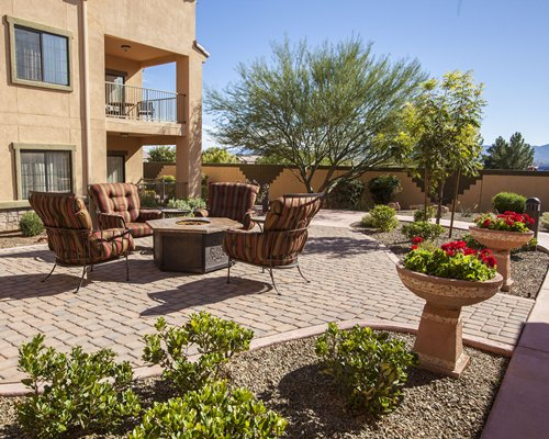 An outdoor patio with campfire alongside the multi story resort.