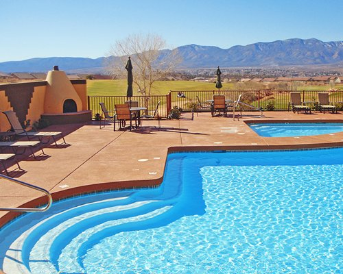 An outdoor swimming pool with chaise lounge chairs and a patio furniture.