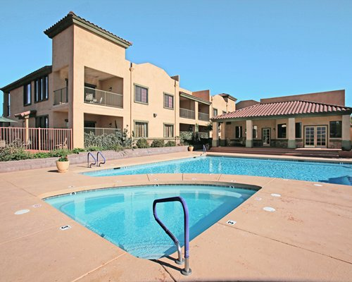 Outdoor swimming pool with a hot tub alongside the units.