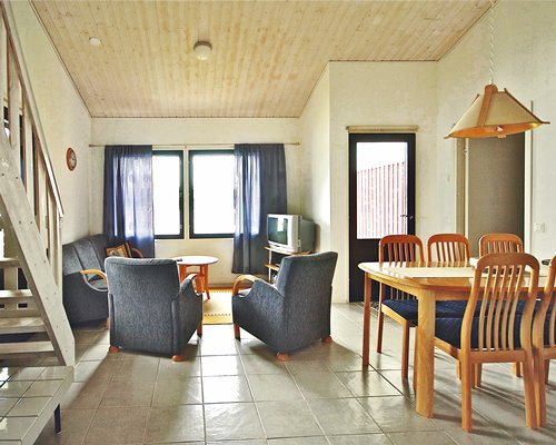 A well furnished living room with a television stairway dining area and outdoor view.