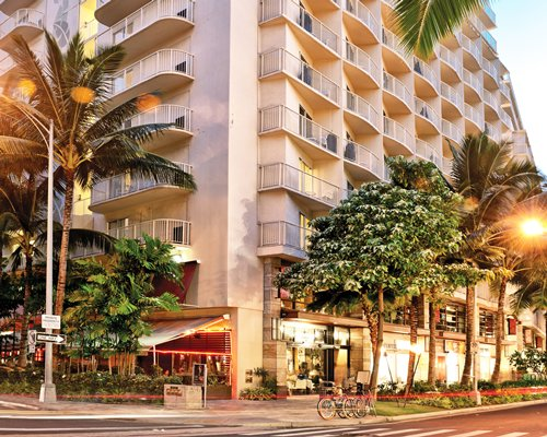 Street view of Wyndham at Waikiki Beach Walk resort with trees.