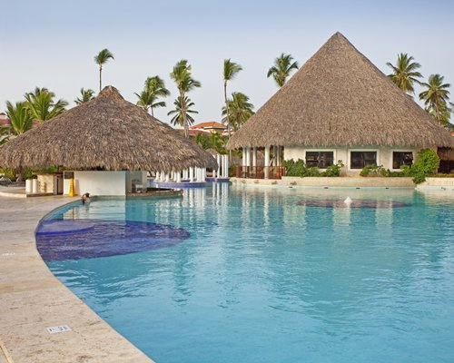 An outdoor swimming pool with thatched sunshades.
