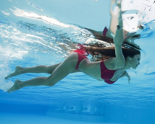 A woman diving in the swimming pool.