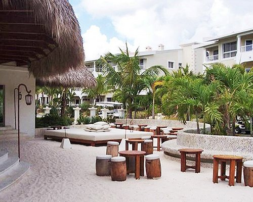 Picnic area alongside a thatched covered unit with palm trees at Club Melia At Paradisus Palma Real.