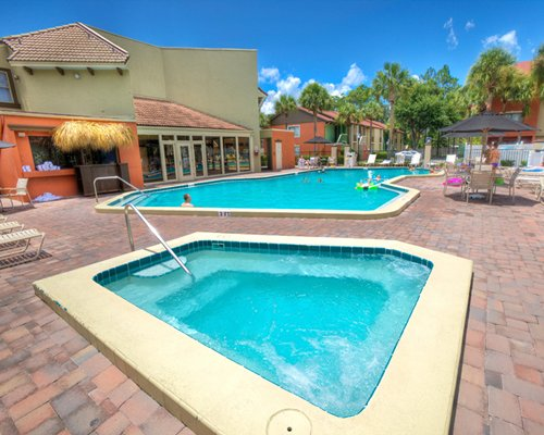 An outdoor hot tub alongside a swimming pool with patio and sunshade.