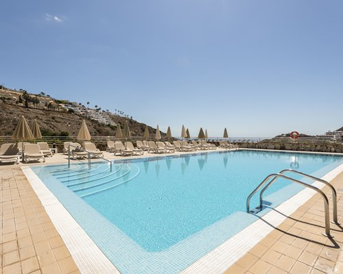An outdoor swimming pool with chaise lounge chairs and sunshades.
